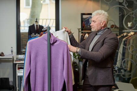 A mature man with gray hair is choosing a turtleneck sweater in a clothing store. A male customer in a wool suit in a boutique.