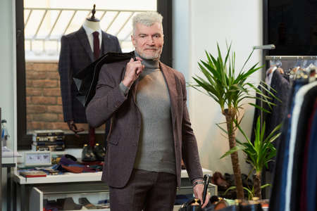 A happy mature man with gray hair and a sporty physique threw two black paper bags behind his back with purchases in a clothing store. A male customer with a beard wears a wool suit in a boutique