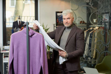 A mature man with gray hair and a sporty physique is choosing a turtleneck sweater in a clothing store. A male customer with a beard wears a wool suit in a boutique. Stock Photo