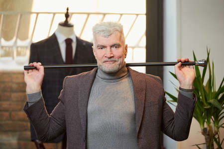 A happy mature man with gray hair and a sporty physique is holding a fiber carbon cane with two hands behind his head in a clothing store. A male customer with a beard wears a suit in a boutique.