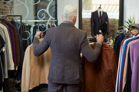 A mature man with gray hair and a sporty physique is going with two jackets on hangers to the fitting room in a clothing store. A male customer with a beard wears a wool suit in a boutique.