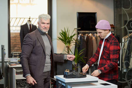 A mature man with gray hair and a sporty physique is posing during the payment for a purchase in a clothing store. A male customer with a beard and a shop assistant in a boutique. Stock Photo