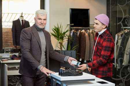 A mature man with gray hair and a sporty physique is applying a cellphone to a point of sale terminal in a clothing store. A satisfied customer with a beard is paying to a shop assistant in a boutique