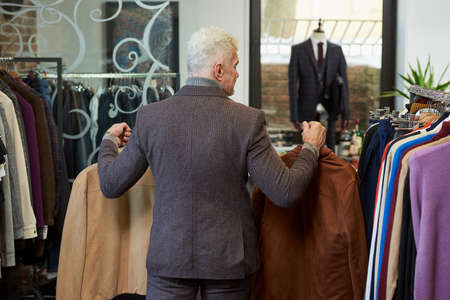 A photo from behind of a mature man with gray hair and a sporty physique is going holding suede jackets to the fitting room in a clothing store. A male customer with a beard wears a suit in a boutique