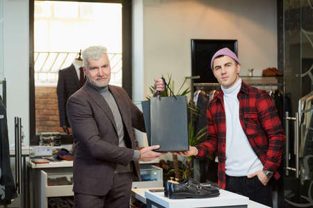 A mature man with gray hair and a sporty physique is taking black paper bags with purchases from a seller in a clothing store. A satisfied shop assistant and a male customer are posing with paper bags Stock Photo