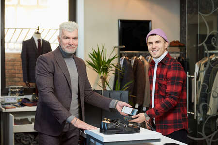 A mature man with gray hair and a sporty physique is applying a cellphone to a point of sale terminal in a store. A satisfied customer with a beard is paying to a smiling shop assistant in a boutique.