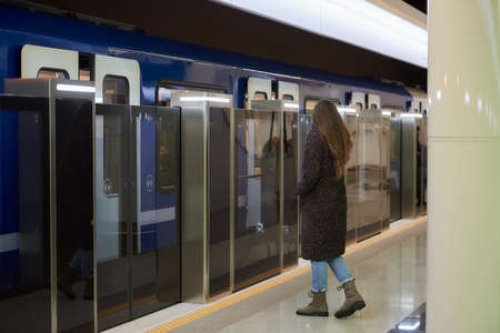A full-length photo of a woman in a medical face mask to avoid the spread of virus who is going to the modern subway car. A girl in a surgical mask is keeping social distance on a metro station.