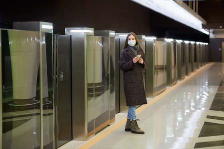 A woman in a medical face mask to avoid the spread of virus is waiting for a train and holding a smartphone at the subway station. A girl in a surgical mask is keeping social distance in metro. Standard-Bild