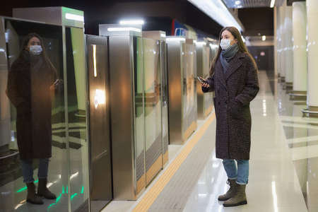 A woman in a medical face mask to avoid the spread of virus is hiding a smartphone while waiting for a train on the subway platform. Girl in a surgical mask is keeping social distance.