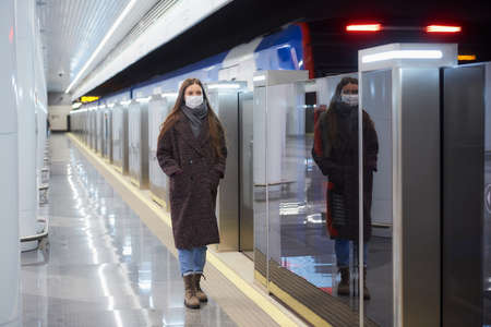 A full-length photo of a woman in a medical face mask to avoid the spread of virus who is standing near the departing train on the subway platform. A girl in a mask is keeping social distance.