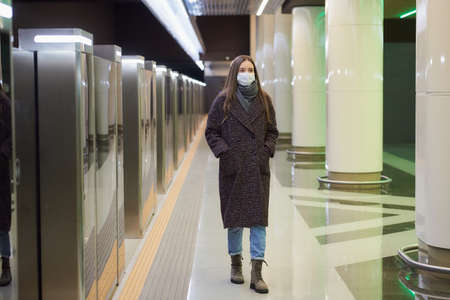 A woman in a medical face mask to avoid the spread of virus is walking while waiting for a train on the subway platform. Girl in a surgical mask is keeping social distance.
