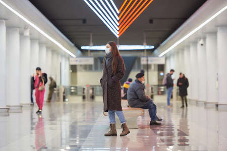 A full-length photo of a woman in a face mask to avoid the spread of who is walking while waiting for a train in the center of a metro station. Girl in a surgical mask is keeping social distance