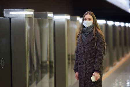 A lady in a medical face mask to avoid the spread of virus is waiting for a train and holding a cellphone at the subway station. A girl in a surgical mask is keeping social distance in the metro