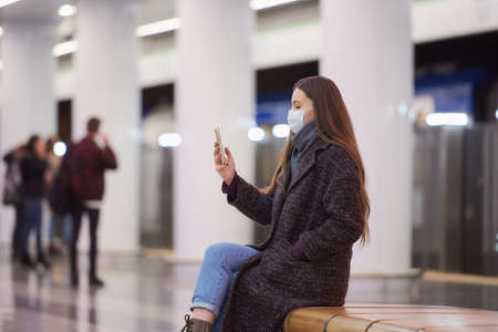 A woman in a medical face mask is sitting in the center of the subway platform with a smartphone and doing a selfie. A girl with long hair in a surgical mask is keeping social distance in the metro.