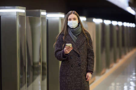 A woman in a medical face mask to avoid the spread of virus is waiting for a train and holding a cellphone at the subway station. A girl in a surgical mask is keeping social distance in metro. Standard-Bild