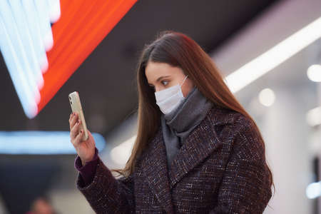 A close portrait of a woman in a medical face mask is sitting at the subway station with a smartphone and doing a selfie. A girl in a surgical mask is keeping social distance in the metro