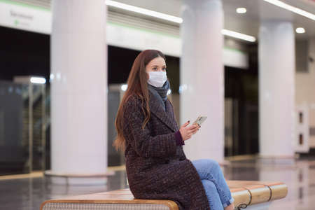 Woman in a medical face mask is sitting in the center of the subway platform with a smartphone and waiting for a train. A girl with long hair in a surgical mask is keeping social distance in the metro