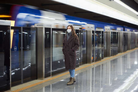 A full-length photo of a woman in a medical face mask to avoid the spread of virus who is waiting for an arriving train on the subway platform. Girl in a surgical mask is keeping social distance Standard-Bild