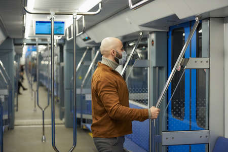 A man with a beard in a medical face mask to avoid the spread of virus is preparing to leave the subway car holding the handrail. A bald guy in a mask is keeping social distance on a train. Standard-Bild