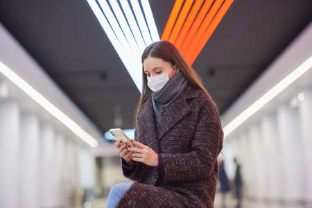 A woman in a medical face mask is sitting in the center of the subway platform with a smartphone and reading the news. A girl with long hair in a surgical mask is keeping social distance in the metro.