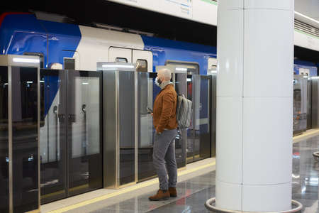 A man in a medical face mask to avoid the spread of is holding a cellphone while waiting for a modern train at the subway platform. A bald guy in a surgical mask is keeping social distance.