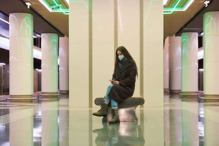 A lonely woman in a medical face mask to avoid the spread of  is sitting using a smartphone on the subway platform. A girl in a surgical mask is keeping social distance in the metro. Standard-Bild