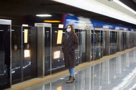 A full-length photo of a woman in a medical face mask to avoid the spread of who is waiting for an arriving train on the subway platform. A girl in a mask is keeping social distance.