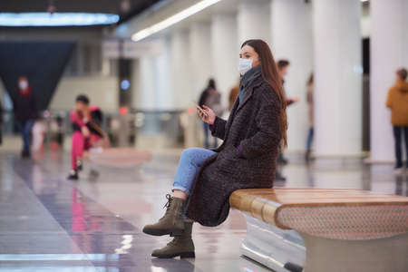 A woman in a medical face mask is sitting in the center of the subway platform with a smartphone and waiting for a train. A girl in a surgical mask is keeping social distance in the metro.