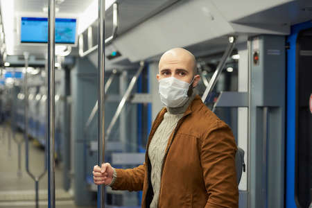 A man with a beard in a medical face mask to avoid the spread of  is standing and holding the handrail in a subway car. A bald guy in a surgical mask is keeping social distance on a train.