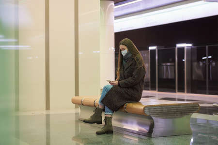 A woman in a medical face mask to avoid the spread of is sitting and using a smartphone on the subway platform. A girl in a surgical mask is keeping social distance in the metro.