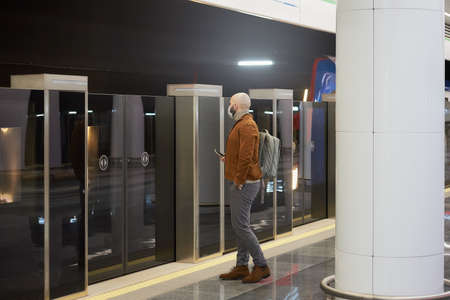 A man in a medical face mask to avoid the spread of is holding a phone while waiting for a modern train on the subway. A bald guy in a surgical mask is keeping social distance.