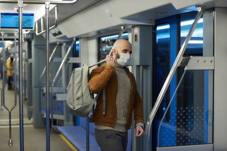 A man with a beard in a face mask to avoid the spread of is putting on a gray backpack while riding a subway car. A bald guy in a surgical mask is keeping social distance on a train. Standard-Bild