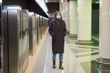 A woman in a medical face mask to avoid the spread of is walking while waiting for a train on the subway platform. Girl in a surgical mask is keeping social distance in the underground.