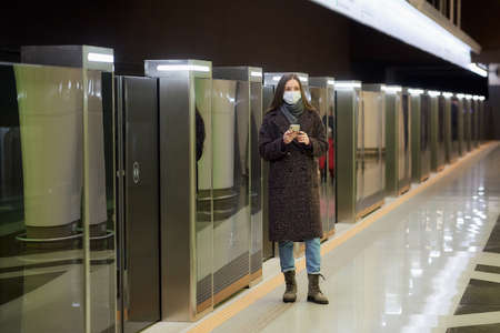 Woman in a medical face mask to avoid the spread of is waiting for a train and holding a phone at the subway station. A girl in a surgical mask against COVID-19 is keeping social distance.