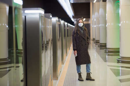 A full-length photo of a lady in a medical face mask to avoid the spread of is waiting for a train and holding a phone on the subway platform. Girl in a surgical mask is keeping social distance