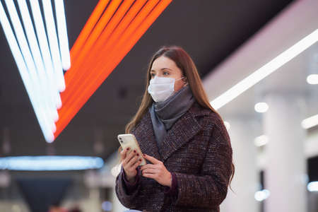 A close portrait of a woman in a medical face mask is sitting at the subway station with a smartphone and waiting for a train. A girl in a surgical mask is keeping social distance in the metro. Standard-Bild