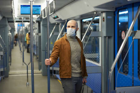 A man with a beard in a medical face mask to avoid the spread of virus is riding and holding the handrail in a subway car. A bald guy in a surgical mask is keeping social distance on a train.
