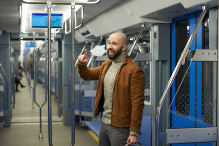 A man with a beard is taking off a medical face mask and smiling in a subway car. A bald guy with a surgical mask is keeping social distance on a train.