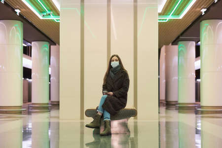 A lonely woman in a medical face mask to avoid the spread of virus is sitting with a smartphone and waiting for a subway train. A girl in a surgical mask is keeping social distance in the metro.