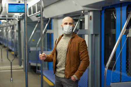 A man with a beard in a medical face mask to avoid the spread of  is riding a subway car and holding the handrail. A bald guy in a surgical mask is keeping social distance on a train.