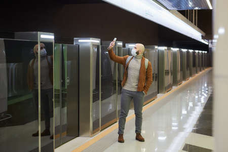 A full-length photo of a man in a face mask who is doing a selfie on a smartphone while waiting for a train at the subway platform. A bald guy in a surgical mask is keeping social distance.