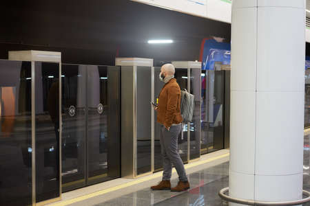 A man in a medical face mask to avoid the spread of virus is holding a smartphone while waiting for a modern train on the subway. A bald guy in a surgical mask is keeping social distance.