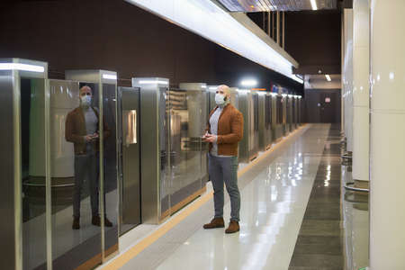 A man in a medical face mask to avoid the spread of virus is holding a smartphone while waiting for a train on the subway. A bald guy in a surgical mask is keeping social distance.