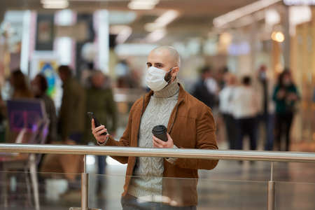 A man with a beard in a face mask is looking to the left and holding a smartphone and a cup of coffee in the shopping center. A bald guy in a surgical mask is keeping social distance.