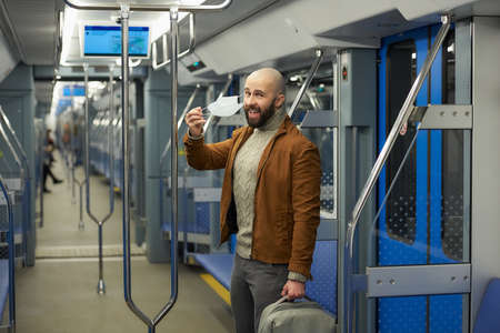 A man with a beard is taking off a medical face mask and smiling in a subway car. A bald guy with a surgical mask against  is keeping social distance on a train.