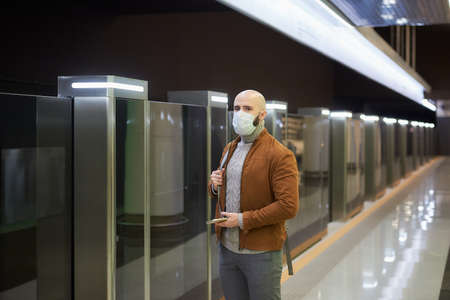 A man in a medical face mask is holding a smartphone and staring to the side while waiting for a train at the subway platform. A bald guy in a surgical mask is keeping social distance.