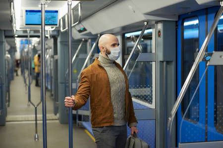 A man with a beard in a medical face mask to avoid the spread of is riding a modern subway car. A bald guy in a surgical mask is keeping social distance on a train.