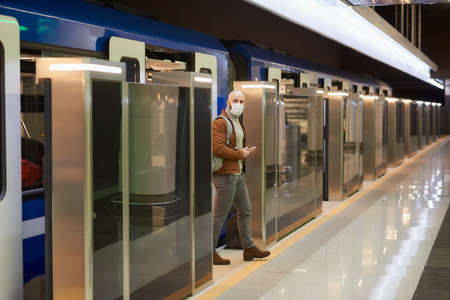 A man in a medical face mask to avoid the spread of is holding a smartphone while leaving a modern subway car. A bald guy in a surgical mask is keeping social distance.