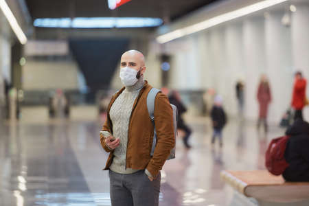 A man in a medical face mask is holding a smartphone and staring to the side while waiting for a train in the center of the subway station. A bald guy in a surgical mask is keeping social distance. Standard-Bild