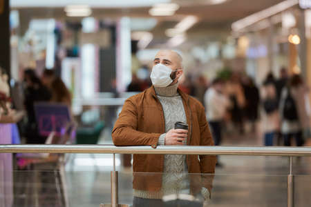 A man in a face mask to avoid the spread of is holding a cup of coffee while waiting in the shopping center. A bald guy in a surgical mask is keeping social distance.